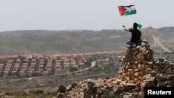 Seorang demonstran melambaikan bendera Palestina di dekat permukiman Yahudi Ofra di dekat Ramallah, Tepi Barat (foto: dok). Liga Arab mengusulkan pertukaran lahan untuk sengketa perbatasan Israel-Palestina.