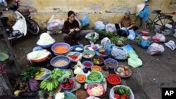 Vietnamese women gather to sell vegetables at a street market.