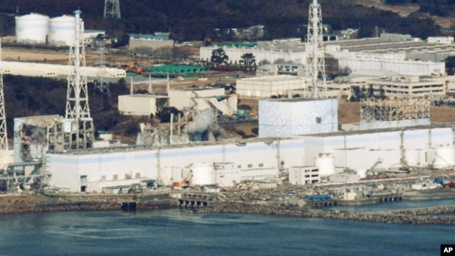 Reactors 1 to 4 (from R to L) of the Fukushima Daiichi nuclear power plant in Fukushima are seen in this picture taken more than 30km (18 miles) offshore from the site shortly before the start of the water-dropping operation, March 17, 2011