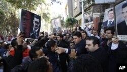 圖中右邊是支持敘利亞總統阿薩德的示威者﹐左邊為反對者。他們上星期在開羅的敘利亞大使館前示威。
