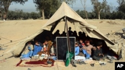 Afghan students attend a school class under a tent in Jalalabad, capital of Nangarhar province, Dec. 16, 2015. According to Afghan Ministry of Education estimates, around 33,000 students have been deprived of education in 58 schools in the Achin, Haskamena, and Kot districts of Nangarhar province.