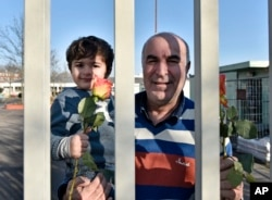 Migrants hold flowers behind the fence of a refugee home in Cologne, Germany, Jan. 22, 2016.
