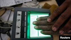 A villager goes through the process of a fingerprint scanner for the Unique Identification (UID) database system at an enrollment center at Merta district in the desert Indian state of Rajasthan, Feb. 22, 2013.