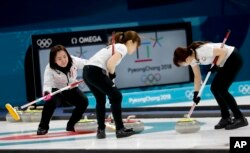 Japan skip Satsuki Fujisawa, left, watches her teammates sweep the ice during a women's curling match against Britain at the 2018 Winter Olympics in Gangneung, South Korea, Feb. 20, 2018.