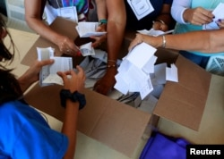 Opposition supporters count votes at a polling station after an unofficial plebiscite against President Nicolas Maduro's government and his plan to rewrite the constitution, in Caracas, Venezuela July 16, 2017.