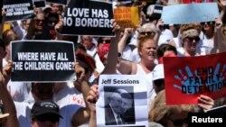 """Una manifestante levanta una foto del fiscal general Jeff Sessions mientras cientos de mujeres y activistas de inmigración marchan en una protesta para exigir """"el fin de las detenciones familiares"""" y contra las políticas de inmigración de la administración Trump, en Washington, el 28 de junio de 2018."""
