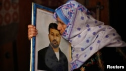 The mother of Palestinian Salah al-Shaer, who has been held by Israel for 20 years, kisses his picture after hearing news on the expected release of her son by Israel, in Khan Younis, in the southern Gaza Strip, Aug. 12, 2013.