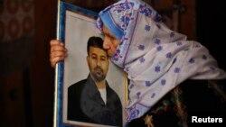 12일 가자지구 남부 칸유니스에서 석방될 예정인 팔레스타인 수감자의 어머니가 아들의 사진에 입맞추고 있다.