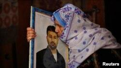 2013年8月12日,巴勒斯坦一名母亲抱着她的儿子的照片,预期她被监禁20年的儿子会在以色列释放的巴勒斯坦囚犯的名单里面。