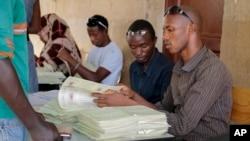 Para pegutas pemilu membagikan kartu suara di ibukota Bujumbura (4/6). (AP/Berthier Mugiraneza)