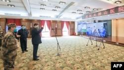 戴着口罩的中国国家主席习近平视察火神山医院时通过视频向新冠病毒感染者和医护人员招手。(2020年3月10日)