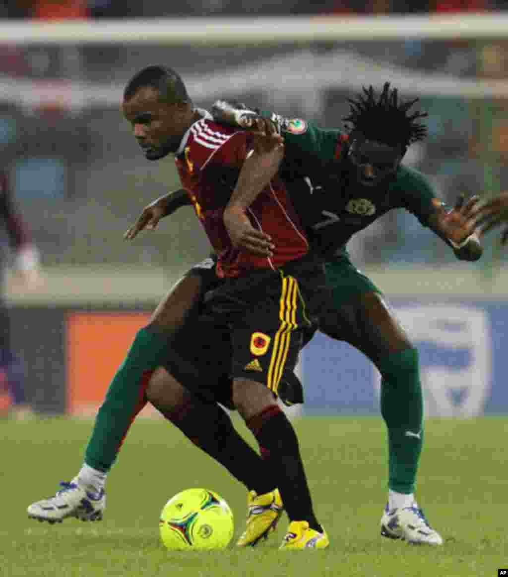 Flavio Amado e Roumba Florent, do Burkina Faso, empenhados numa jogada durante o primeiro jogo das Palancas Negras, no CAN 2012, no Estádio de Malabo, a 22 de Janeiro