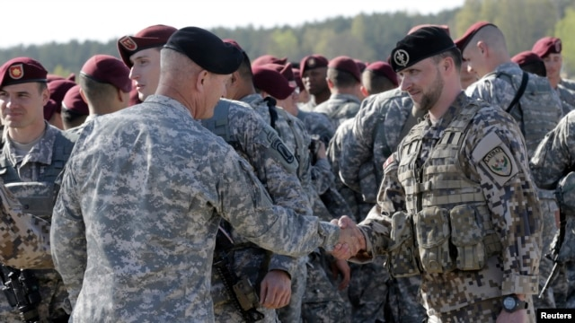 FILE - A Latvian army officer (R) shakes hands with his U.S. counterpart as a contingent of U.S. Army paratroopers arrive at the airport in Riga April 24, 2014.