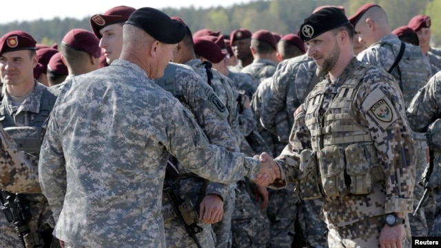 FILE - A Latvian army officer (R) shakes hands with his U.S. counterpart as a contingent of U.S. Army paratroopers arrive at the airport in Riga, Latvia, April 24, 2014.