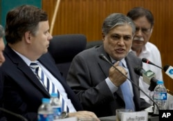 FILE - Then-Pakistani Finance Minister Muhammad Ishaq Dar, center, addresses a news conference with Jeffrey Franks, left, who then was the IMF mission chief for Pakistan, at the finance ministry in Islamabad, Pakistan, July 4, 2013. At the time, Pakistan and the IMF reached agreement on a bailout plan.