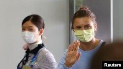 Pelari cepat Belarus, Krystsina Tsimanouskaya, yang berlindung di Kedutaan Besar Polandia di Tokyo, melambaikan tangan sebelum menaiki pesawat untuk terbang ke Wina, di Bandara Internasional Narita, Tokyo, Jepang, Rabu, 4 Agustus 2021. (Foto: Issei Kato/Reuters)