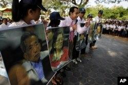 លោក នេត្រ ភក្ត្រា (កណ្តាល) មន្ត្រីសាលាក្តីខ្មែរក្រហមពន្យល់សិស្សានុសិស្សដោយមានការបង្ហាញរូបភាពអតីតមេដឹកនាំខ្មែរក្រហម នៅក្នុងវេទិកាសាធារណៈមួយក្នុងក្រុងភ្នំពេញកាលពីថ្ងៃទី១៨ ខែវិច្ឆិកា ឆ្នាំ២០១១។ សិស្សរាប់រយនាក់ចូលរួមវេទិកាសាធារណៈដែលរៀចចំដោយសាលាក្តីដែលគាំទ្រដោយអង្គការសហប្រជាជាតិ។ (AP Photo/Heng Sinith)