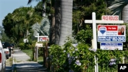 """For Sale"" signs line the front yards of several houses in a Hollywood, Florida neighborhood (file)"
