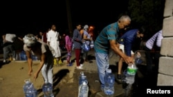 People collect water from a spring in the Newlands suburb as fears over the city's water crisis grow in Cape Town, South Africa, Jan. 25, 2018.