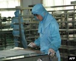 工人在太阳能模组生产线工作