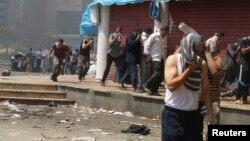 Manifestantes egípcios momentos depois da intervenção das forças de segurança para despersar as concentrações anti-governamentais no Cairo