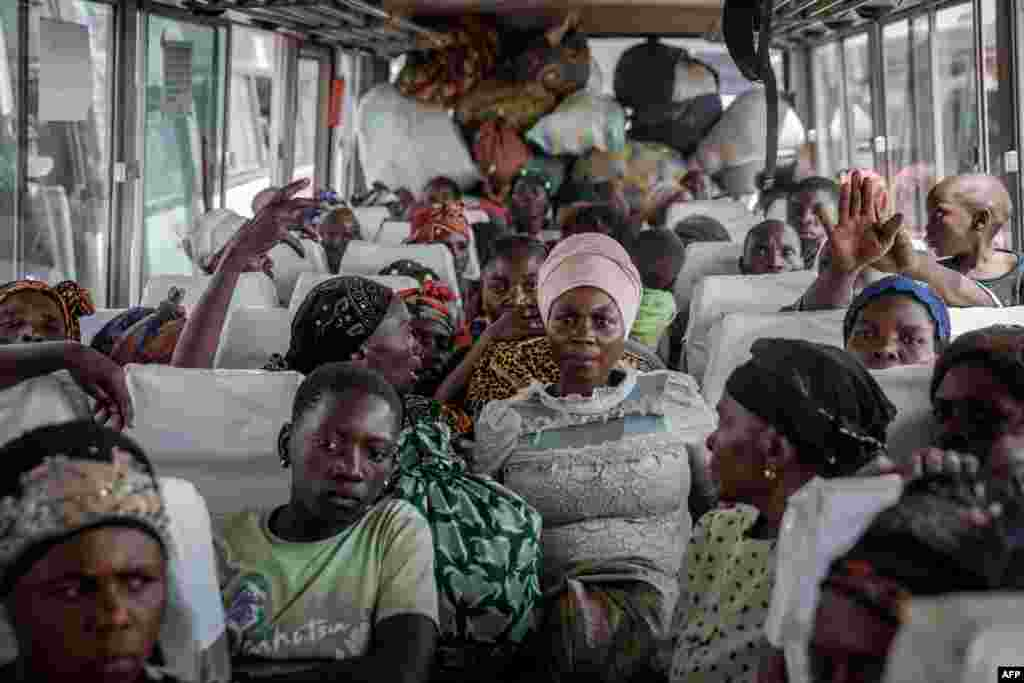 Displaced people who fled Goma, Democratic Republic of the Congo, after the eruption of the Nyiragongo volcano sit on a bus in Sake with their belongings, waiting to be taken home.