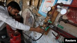 A man gauges liquefied petroleum gas in a cylinder at his makeshift shop in Karachi on April 22, 2010. Pakistan is battling a chronic energy shortage, stifling industry and angering the public.