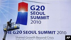 A worker adjusts a giant banner at the entrance to the G-20 Summit in Seoul, South Korea (file photo)
