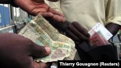 Deux personnes échangent de l'argent à Abidjan, le 31 décembre 2004.