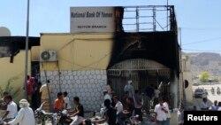 Warga melewati bank yang rusak setelah diserang oleh kawanan bersenjata. (Foto: dok)