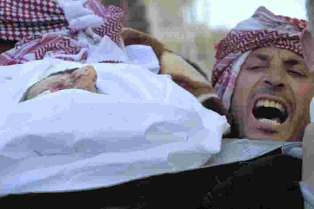 Un hombre canta mensajes contra el gobierno mientras carga el cuerpo de Abdulziz Abu Ahmed Khrer, quien recibió un disparo de un francotirador del ejército sirio.