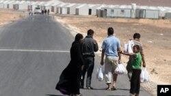 Satu keluarga pengungsi Suriah berjalan menuju kamp pengungsi Azraq yang baru dibuka di Yordania dekat perbatasan Suriah (30/4).