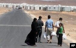 个叙利亚难民家庭正在向约旦阿兹拉克难民营走去。