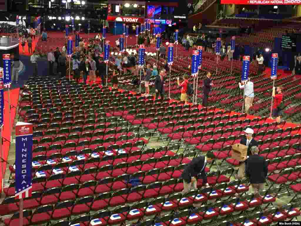 Convention workers leave a booklet that lists the convention delegates and a nightly schedule on the delegates' seats at Quicken Loans Arena before the Republican convention begins, in Cleveland, July 19, 2016.