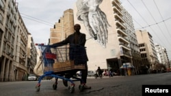 FILE - A migrant living in Greece pushes a shopping cart with scrap in front of a building covered with street art in Athens.