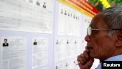 Một cử tri đọc hồ sơ của các ứng viên tại một trạm bỏ phiếu ở Hà Nội, 22/5/2016.