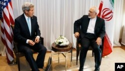 U.S. Secretary of State John Kerry, left, waits with Iranian Foreign Minister Mohammad Javad Zarif before a meeting in Geneva, Switzerland, Jan. 14, 2015.