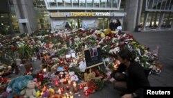 在俄罗斯圣彼得堡普尔科沃机场外为西奈半岛上空失事的俄罗斯航班死难者设立的一个祭奠地点,一名妇女在献花。(2015年11月4日)