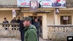 一名叙利亚警官走过萨尔玛城一座挂有叙利亚总统阿萨德画像的房屋 (资料照片)