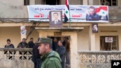 FILE - A Syrian police officer walks past a group of local people standing at a building with a portrait of Syrian President Bashar al-Assad in Salma, Syria, Jan. 22, 2016.