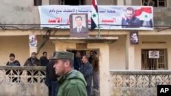 Sĩ quan cảnh sát Syria đi ngang qua nhóm người địa phương đứng tại một tòa nhà với bức chân dung Tổng thống Syria Bashar al-Assad ở Salma, Syria, ngày 22/1/2016.