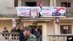 រូបភាពឯកសារ៖ ប៉ូលិសម្នាក់ដើរកាត់ប្រជាជនមួយក្រុមដែលកំពុងឈរនៅខាងមុខអគារដែលមានរូបថតប្រធានាធិបតីស៊ីរី Bashar al-Assad in Salma កាលពីថ្ងៃទី២២ មករា ២០១៦