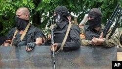 Tentara Ukraina berada di atas kendaraan ketika mereka meninggakan lokasi pertempuran di Mariupol, Ukraine timur, 13/6/2014.