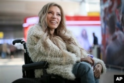 FILE - In this file photo dated March 14, 2017, Russian singer Yulia Samoylova who was chosen to represent Russia in the 2017 Eurovision Song Contest, poses while sitting in a wheelchair at Sheremetyevo airport outside Moscow, Russia.