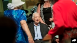 FILE - Former president Jimmy Carter sits to pose for photos after teaching Sunday School class at Maranatha Baptist Church in his hometown Aug. 23, 2015, in Plains, Georgia.