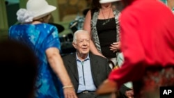 Former president Jimmy Carter, sits to pose for photos after teaching Sunday School class at Maranatha Baptist Church in his hometown of Plains, Georgia, Aug. 23, 2015.