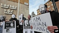 Supporters of WikiLeaks founder Julian Assange, some wearing masks depicting him and holding placards, participate at a demonstration outside the Swedish Embassy in London, Dec 13, 2010