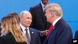 លោកប្រធានាធិបតី ដូណាល់ ត្រាំ ដើរកាត់លោកប្រធានាធិបតី Vladimir Putin នៅពេលអស់លោកថតរូបជាក្រុម នៅក្នុងកិច្ចប្រជុំ G-20 ក្នុងក្រុង Buenos Aires ប្រទេសអាហ្សង់ទីន កាលពីថ្ងៃទី៣០ ខែវិច្ឆិកា ឆ្នាំ២០១៨។