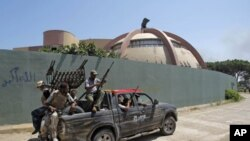 Rebel fighters seen inside the main Moammar Gadhafi compound in Bab al-Aziziya in Tripoli, Libya, August 24, 2011