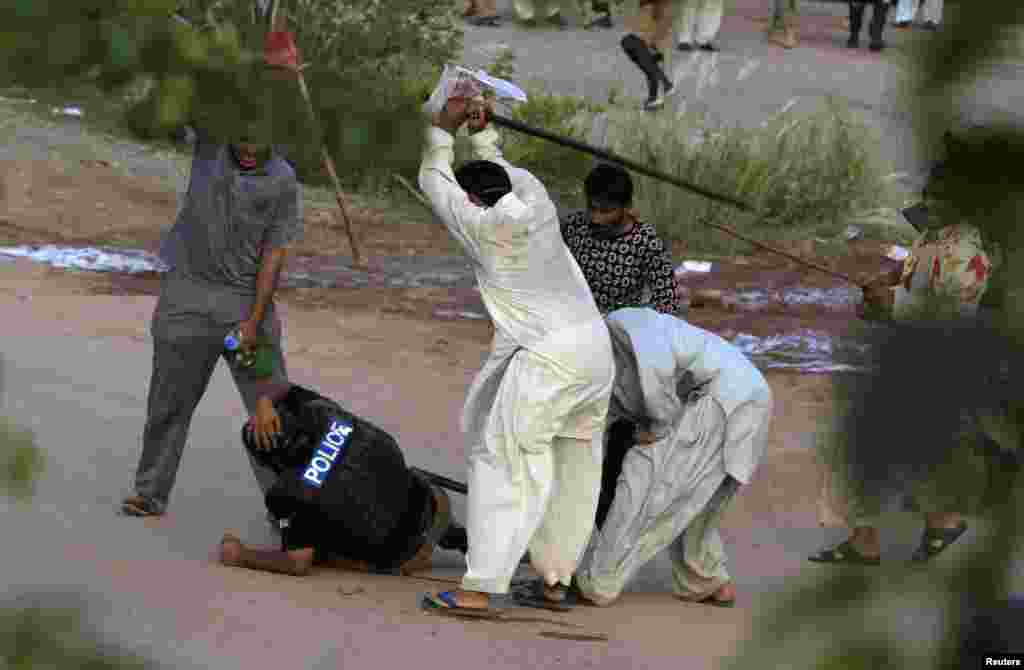 Anti-government protesters beat a riot policeman after clashes during the Revolution March in Islamabad, Pakistan.